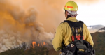 Image of a firefighter as a lookout up on a ridge overseeing the fire across the valley.