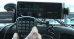 Photo of hand holding keypad to a mobile radio mounted on the dash board of a vehicle.