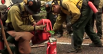 Photo of wildland firefighters pouring fuel into a drip torch tank.
