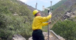 Image of a firefighter adjusting a RAWS unit in a canyon with brush and rocks.