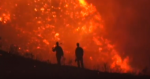 Photo of silhouette of fire fighters walking up hill with flames in background.