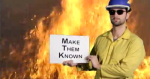 "Fire fighter standing in front of flames holding sign that says ""make them known""."