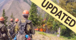 "Group of wildland firefighters stand on hill looking down at flames in trees. With ""UPDATED"" banner."