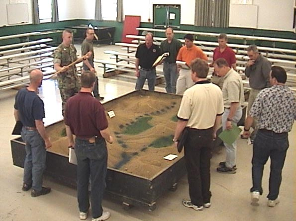 Photo of group of students standing around a sandbox used for tactical games.